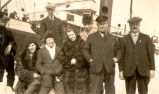 S.S. Viking Disaster: Seven men and two women standing near the S.S. Sagona.