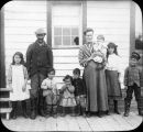 Man and woman with seven children, standing in front of a building