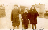 ''Yvonne, Jim and Patricia with their snowman behind the stone building''