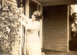 Kathleen (Forward) Rorke fixing some flowers on the front step of her home, Dunrovin, Carbonear